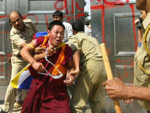 Indian policemen arrest a protesting Tibetan monk during a demonstration at the Chinese Embassy in New Delhi, 10 October 2007. Some 40 Tibetan youth, Buddhist monks and nuns entered the embassy premises where they were beaten by Embassy staff and police. The demonstrators condemned and demanded the withdrawal of China's latest religious measures on the recognition of 'living Buddhas'. AFP PHOTO/RAVEENDRAN